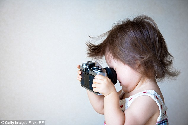 1414557743162_wps_4_Girl_holding_camera.jpg